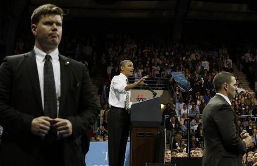 24 آوریل 2012: اوباما که توسط بادیگاردهایش محافظت می شود در حال سخنرانی در دانشگاه کارولینای شمالی در چپل هیل. REUTERS/Larry Downing