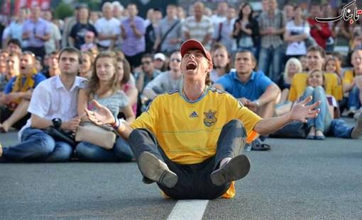 یک طرفدار تیم ملی اوکراین در یکی از خیابانهای کیف که از تلویزیون شهری، بازی افتتاحیه جام ملتها را نگاه میکند. Sergei Supinsky / AFP - Getty Images
