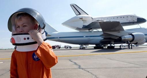 پسر بچه ای که به تماشای فرود انیور در فرودگاه الینگتون (هوستون) آمده، کلاه فضایی خود را تنظیم می کند. (AP Photo/David J. Phillip)