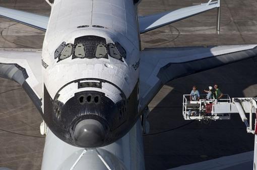 لازم است که پیش از آغاز سفر، پوشش پنجره های شاتل برداشته شود. (NASA/Kim Shiflett)